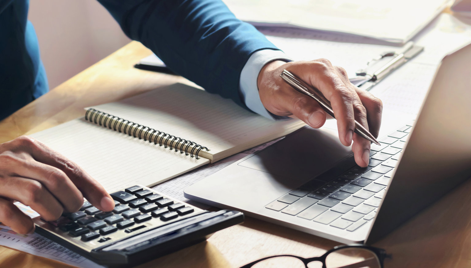 businessman working on desk with using calculator and computer i